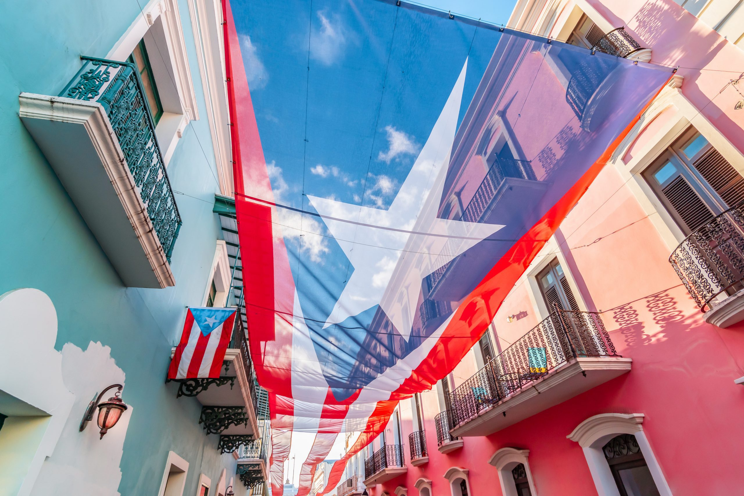 Colorful image of city centre of San Juan with large Puerto Rican flag above the street. Blue and pink buildings in the street. Sunny day. Red and white stripes, white star and blue colored national flag of Puerto Rico.